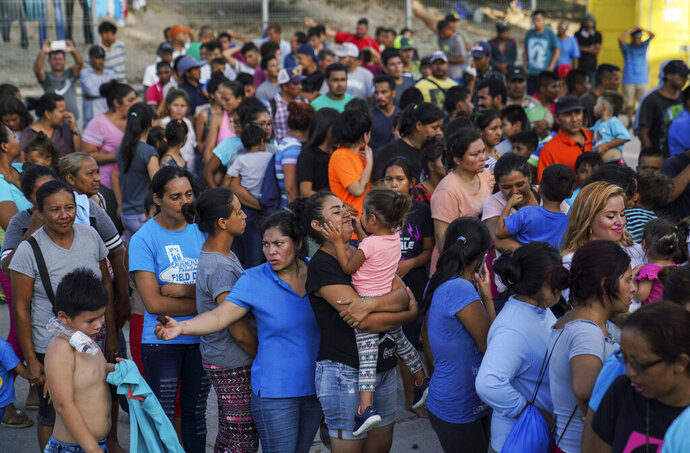 "In this Aug. 30, 2019, photo, migrants, many who were returned to Mexico under the Trump administration's ""Remain in Mexico,"" program wait in line to get a meal in an encampment near the Gateway International Bridge in Matamoros. Many shelters at the Mexico border are at or above capacity already, and some families have been sleeping in tents or on blankets in the blistering summer heat. (AP Photo/Veronica G. Cardenas)"
