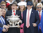 Owners Kenny Trout, right, and Teo Ah Khing hold the August Belmont trophy after their horse Justify won the Triple Crown at the 150th running of the Belmont Stakes horse race Saturday, June 9, 2018, in Elmont, N.Y. (AP Photo/Julio Cortez)