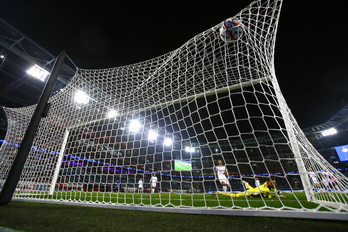 Lokomotiv's goalkeeper Guilherme dives but fails to save the goal from Atletico Madrid's Jose Gimenez during the Champions League Group A soccer match between Lokomotiv Moscow and Atletico Madrid in Moscow, Russia, Tuesday, Nov. 3, 2020. (Maxim Shemetov/Pool via AP)