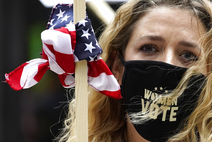Lindsey Schwartz wears a mask with a message as she holds a sign during the Women's March in downtown Chicago, Saturday, Oct. 17, 2020.  Dozens of Women's March rallies were planned from New York to San Francisco to signal opposition to President Donald Trump and his policies, including the push to fill the seat of late Supreme Court Justice Ruth Bader Ginsburg before Election Day. (AP Photo/Nam Y. Huh)