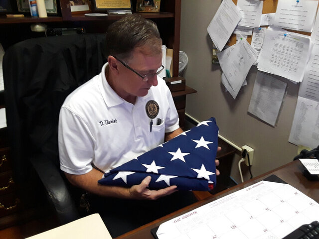 In this Nov. 2, 2019 photo, Danny Theriot, the Terrebonne Coroner's Office chief investigator, holds a flag in his office in Houma, La. Theriot says he believes the bodies of unclaimed military veterans deserve better than a simple pauper burial. He has been providing military burials for the bodies of unclaimed veterans since 2015. (Dan Copp/The Houma Daily Courier via AP)