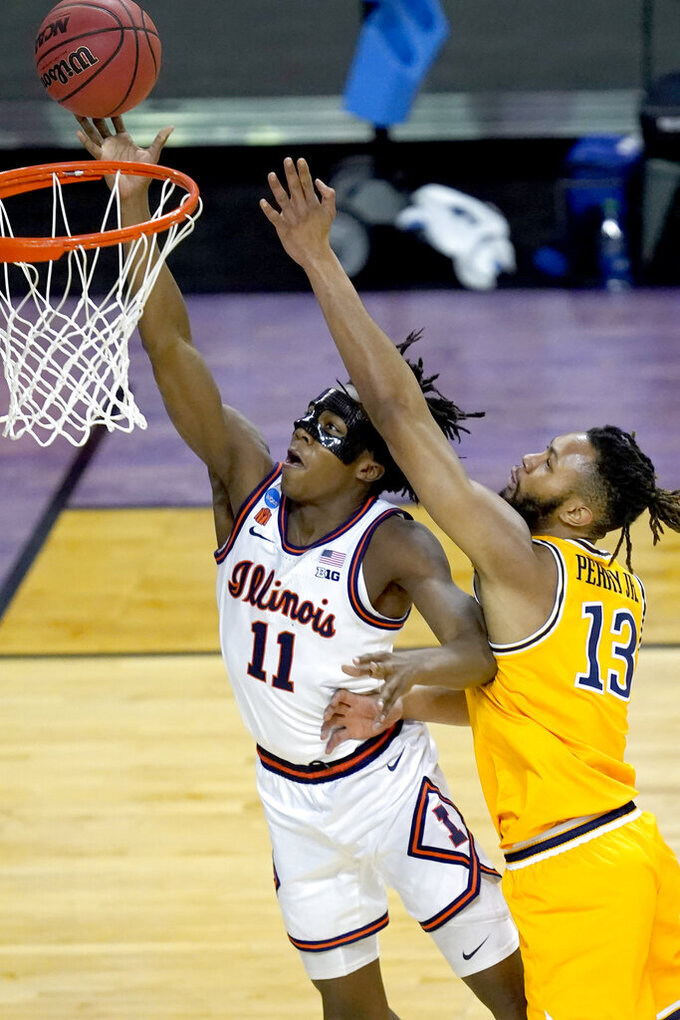 Illinois guard Ayo Dosunmu (11) scores past Drexel's Tim Perry Jr. during the second half of a first round NCAA college basketball tournament game Friday, March 19, 2021, at the Indiana Farmers Coliseum in Indianapolis. Illinois won 78-49. (AP Photo/Charles Rex Arbogast)