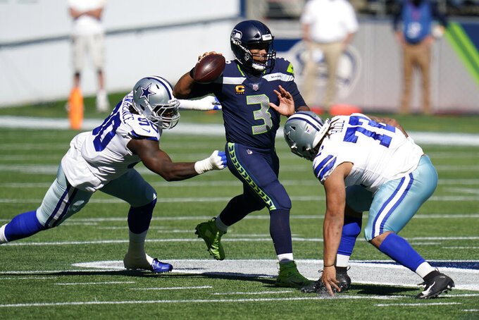 Seattle Seahawks quarterback Russell Wilson passes under pressure from Dallas Cowboys' Trysten Hill (72) and DeMarcus Lawrence (90) during the first half of an NFL football game, Sunday, Sept. 27, 2020, in Seattle. (AP Photo/Elaine Thompson)