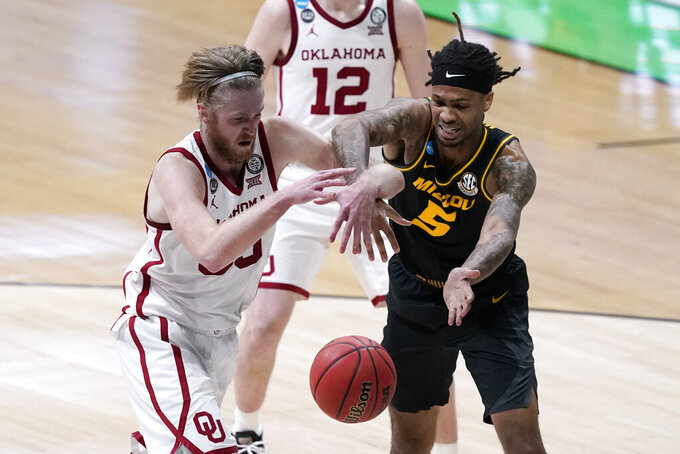 Oklahoma forward Brady Manek, left, fights for a loose ball with Missouri forward Mitchell Smith, right, during the second half of a first-round game in the NCAA men's college basketball tournament at Lucas Oil Stadium, Saturday, March 20, 2021, in Indianapolis. (AP Photo/Darron Cummings)