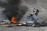 An anti-government protester drops oil on burning tires and wood during ongoing protests after weeks of calm in Beirut, Lebanon, Tuesday, Jan. 14, 2020. Lebanon is facing its worst economic crisis in decades, with the local currency losing over 60% of its value to the dollar over the last weeks while sources of foreign currency have dried up. (AP Photo/Hussein Malla)