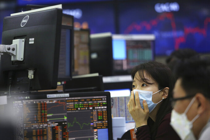 A currency trader watches monitors at the foreign exchange dealing room of the KEB Hana Bank headquarters in Seoul, South Korea, Thursday, Jan. 21, 2021. Asian shares rose Thursday on optimism over the new U.S. administration that earlier set off a rally on Wall Street. (AP Photo/Ahn Young-joon)