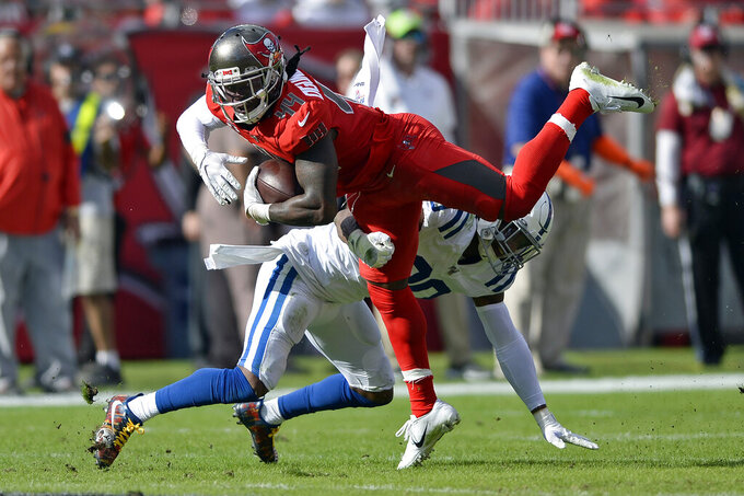 Tampa Bay Buccaneers running back Dare Ogunbowale (44) gets upended by Indianapolis Colts defensive back George Odum (30) during the first half of an NFL football game Sunday, Dec. 8, 2019, in Tampa, Fla. (AP Photo/Jason Behnken)