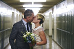 In this Saturday, March 10, 2018 photo, newlyweds Jenn Sudol and Chris Gash kiss as they are married in front of their old high school lockers at Clifton High School, in Clifton, N.J. The couple met in 1989 when they were freshman at the school.  (Anne-Marie Caruso /The Record via AP)
