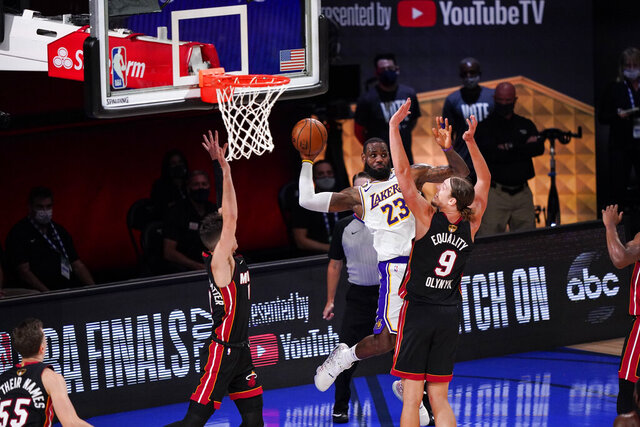 Los Angeles Lakers' LeBron James (23) passes the ball against Miami Heat's Kelly Olynyk (9) and Miami Heat's Tyler Herro (14) during the second half in Game 3 of basketball's NBA Finals, Sunday, Oct. 4, 2020, in Lake Buena Vista, Fla. (AP Photo/Mark J. Terrill)