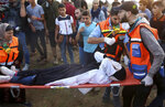 Medics evacuate their wounded colleague, from near the fence of the Gaza Strip border with Israel during a protest east of Gaza City, Friday, Nov. 9, 2018. Gaza's Hamas rulers said Friday that deadly protests along Gaza-Israel perimeter fence have achieved some goals; $15 million from Qatar to help pay the salaries of civil servants. (AP Photo/Adel Hana)