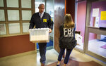 Agents and support staff with the FBI carry out documents and computers from the Muncie City Hall after raiding two Muncie Sanitary District offices inside the building in Muncie, Ind., Tuesday, July 16, 2019. Several other locations across the city were also visited by the FBI. (Corey Ohlenkamp/The Star Press via AP)