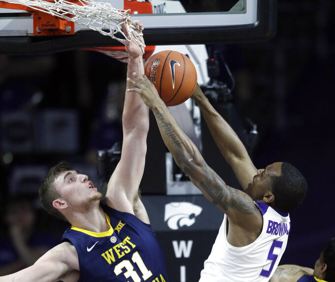 West Virginia forward Logan Routt (31) blocks a shot by Kansas State guard Barry Brown Jr. (5) during the first half of an NCAA college basketball game in Manhattan, Kan., Wednesday, Jan. 9, 2019. (AP Photo/Orlin Wagner)