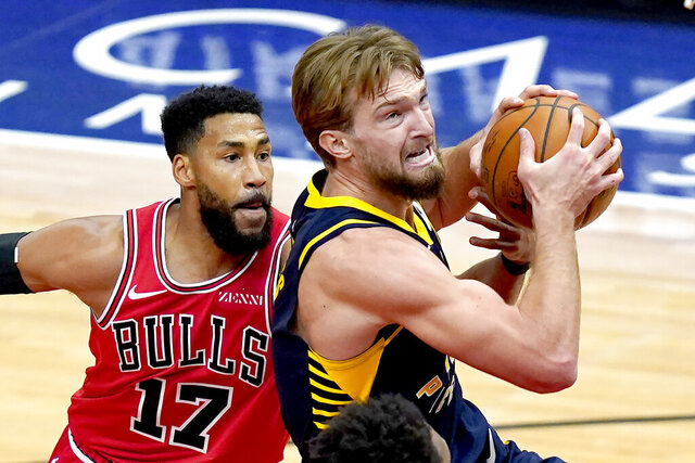 Indiana Pacers' Domantas Sabonis, right, drives past Chicago Bulls' Garrett Temple during the second half of an NBA basketball game Saturday, Dec. 26, 2020, in Chicago. (AP Photo/Charles Rex Arbogast)