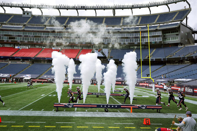 The New England Patriots run onto the field surrounded by empty Gillette Stadium seats, absent of fans due to the COVID-19 pandemic ,before an NFL football game against the Las Vegas Raiders, Sunday, Sept. 27, 2020, in Foxborough, Mass. (AP Photo/Charles Krupa)