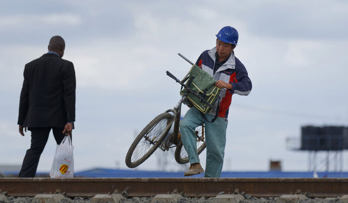 FILE - In this Nov. 23, 2016, a Chinese worker on the Nairobi-Mombasa railway carries his bicycle, used for getting around the construction site, across train tracks near Syokimau station in Nairobi, Kenya. China's large-scale investments in Africa are starting to find pushback in Uganda. Some critics worry the East African nation is using oil it hasn't even begun to produce to borrow hundreds of millions of dollars for infrastructure projects. (AP Photo/Ben Curtis)