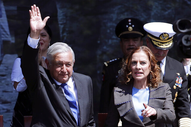 Mexico's President Andres Manuel Lopez Obrador waves during an event marking Army Day at the Zocalo, accompanied by first lady Beatriz Gutierrez Muller, in Mexico City, Wednesday, Feb. 19, 2020. (AP Photo/Marco Ugarte)