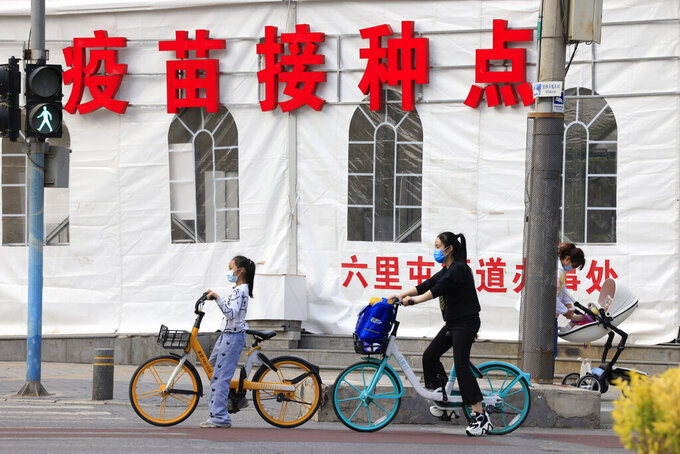 A woman tends to a baby in a pram as a girl waits to cross a junction near a vaccination site in Beijing on May 11, 2021. If China is to meet its tentative goal of vaccinating 80% of its population against the coronavirus by the end of the year, tens of millions of children may have to start rolling up their sleeves. (AP Photo/Ng Han Guan)