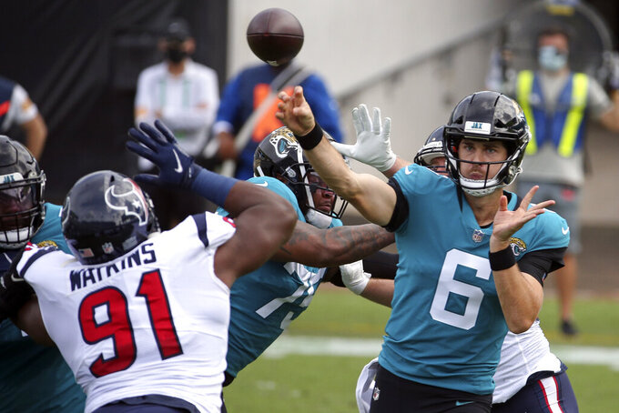 Jacksonville Jaguars quarterback Jake Luton (6) throws a pass over Houston Texans defensive end Carlos Watkins (91) during the first half of an NFL football game, Sunday, Nov. 8, 2020, in Jacksonville, Fla. (AP Photo/Stephen B. Morton)