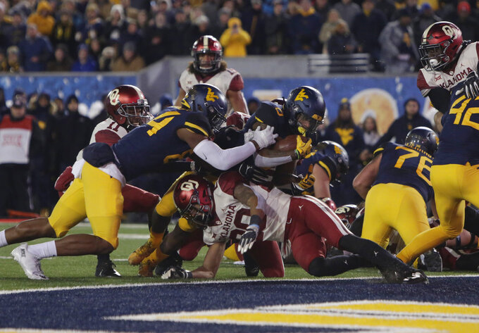 Oklahoma safety Robert Barnes (20) tries to stop West Virginia running back Kennedy McKoy (6), who scored a touchdown during the first half of an NCAA college football game Friday, Nov. 23, 2018, in Morgantown, W.Va. (AP Photo/Raymond Thompson)