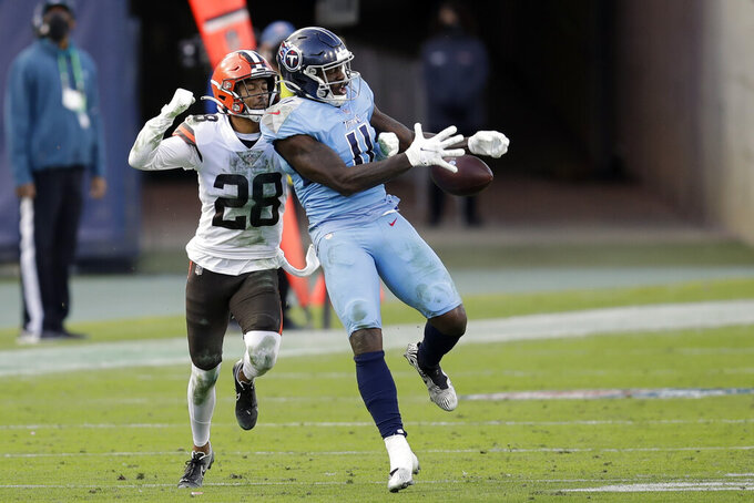 Tennessee Titans wide receiver A.J. Brown (11) can't hold onto a pass as he is defended by Cleveland Browns cornerback Kevin Johnson (28) in the second half of an NFL football game Sunday, Dec. 6, 2020, in Nashville, Tenn. (AP Photo/Ben Margot)