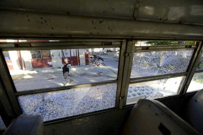 A soldier walks past City Hall that is riddled with bullet holes after a weekend gun battle, in Villa Union, Mexico, Tuesday, Dec. 3, 2019. Villa Union residents said Tuesday they fear a return to the bad old days of 2010-2013. The small town is 12 miles (20 kilometers) from the town of Allende, the site of a 2011 massacre in which the Zetas killed at least 70 people. (AP Photo/Eduardo Verdugo)