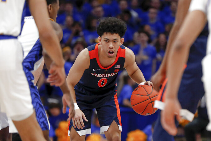 Virginia's Kihei Clark (0) brings the ball down court pst Pittsburgh's Xavier Johnson, left, during the first half of an NCAA college basketball game, Saturday, Feb. 22, 2020, in Pittsburgh. (AP Photo/Keith Srakocic)