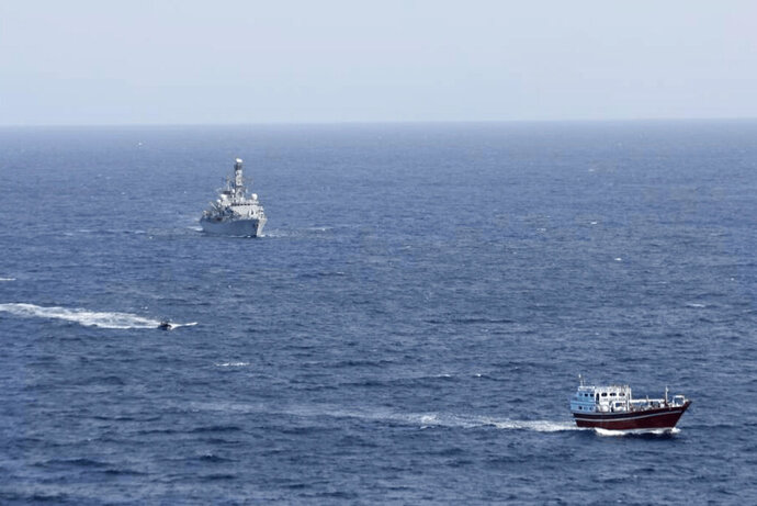 In this photo released by Combined Maritime Forces, a boarding team from a British royal navy vessel, the HMS Montrose, transits towards a stateless dhow, a traditional cargo ship that plies the Persian Gulf and surrounding waters, in the northern Arabian Sea, Wednesday, Oct. 14, 2020. The British royal navy seized 450 kilograms 450 kilograms (990 pounds) of methamphetamine from the dhow in the largest-ever bust by a joint maritime operation in the region. (Combined Maritime Forces via AP)