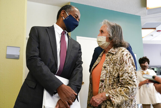 Housing and Urban Development Secretary Ben Carson, left, talks with resident Maggie Rawland, right, after touring the Plymouth Place senior housing facility with Iowa Gov. Kim Reynolds, Tuesday, Sept. 22, 2020, in Des Moines, Iowa. (AP Photo/Charlie Neibergall)