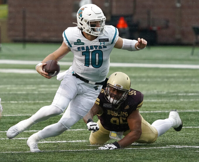 Coastal Carolina's Grayson McCall (10) scrambles past Texas State's Nico Ezidore (95) during the first half of an NCAA college football game in San Marcos, Texas, Saturday, Nov. 28, 2020. (AP Photo/Chuck Burton)