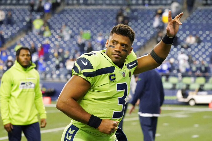 Seattle Seahawks quarterback Russell Wilson waves to fans as he leaves the field after an NFL football game against the Los Angeles Rams, Thursday, Oct. 7, 2021, in Seattle. Wilson suffered a hand injury and the Rams won 26-17. (AP Photo/Elaine Thompson)