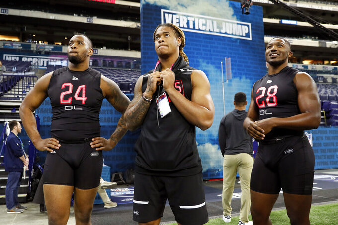 Ohio State defensive lineman Chase Young, center, watches a drill with Alabama defensive lineman Raekwon Davis, left, and Florida defensive lineman Jonathan Greenard, right, at the NFL football scouting combine in Indianapolis, Saturday, Feb. 29, 2020. (AP Photo/Charlie Neibergall)