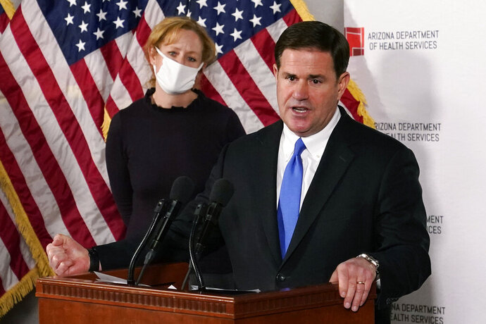 """FILE - In this Dec. 2, 2020, file photo, Arizona Gov. Doug Ducey answers a question about the arrival of a COVID-19 vaccine in Arizona, while Arizona Department of Health Services Director Dr. Cara Christ listens in Phoenix. As Arizona experienced periodic spikes in COVID-19 cases since last spring, Ducey frequently resisted calls to take strong measures. He has declined to institute a statewide mask mandate, allowed school districts to mostly make their own choices and allowed businesses to stay open. All of those choices by the Republican governor are now getting renewed scrutiny as the Grand Canyon state becomes what health officials call the latest """"hot spot of the world"""" because of soaring case loads. (AP Photo/Ross D. Franklin, Pool, File)"""