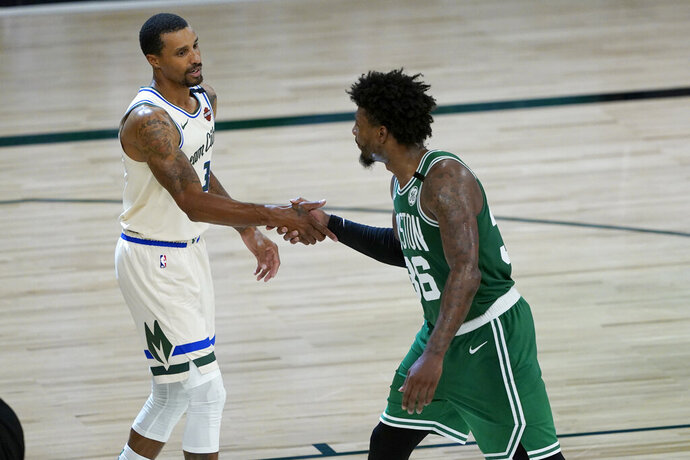 Milwaukee Bucks' George Hill, left, and Boston Celtics' Marcus Smart shake hands following an NBA basketball game Friday, July 31, 2020, in Lake Buena Vista, Fla. (AP Photo/Ashley Landis, Pool)