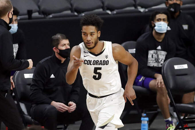 Colorado's D'Shawn Schwartz reacts after sinking a 3-point shot during the first half of an NCAA college basketball game against Washington, Sunday, Dec. 20, 2020, in Las Vegas. (AP Photo/Isaac Brekken)