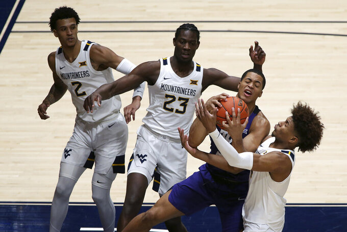 Texas Christian forward Jaedon LeDee (23) is defended by West Virginia forwards Jalen Bridges (2), Seny Ndiaye (23), and guard Miles McBride (4) during the second half of an NCAA college basketball game Thursday, March 4, 2021, in Morgantown, W.Va. (AP Photo/Kathleen Batten)