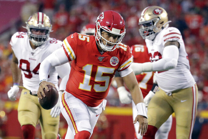 Kansas City Chiefs quarterback Patrick Mahomes (15) scrambles away from San Francisco 49ers defensive lineman Damontre Moore (92) and defensive end Solomon Thomas (94) during the first half of an NFL preseason football game in Kansas City, Mo., Saturday, Aug. 24, 2019. (AP Photo/Charlie Riedel)