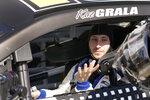 Kaz Grala prepares to go out on the speedway as a crew member hands him his helmet during a NASCAR Daytona 500 auto race practice session at Daytona International Speedway, Wednesday, Feb. 10, 2021, in Daytona Beach, Fla. (AP Photo/John Raoux)