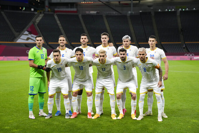 Romania starting players pose for a photo prior to a men's soccer match against New Zealand at the 2020 Summer Olympics, Wednesday, July 28, 2021, in Sapporo, Japan. (AP Photo/Silvia Izquierdo)
