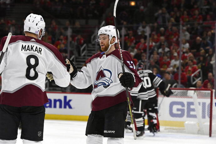 Colorado Avalanche's Cale Makar (8) celebrates with teammate J.T. Compher (37) after scoring during the first period of an NHL hockey game against the Chicago Blackhawks Friday, Nov. 29, 2019, in Chicago. (AP Photo/Paul Beaty)