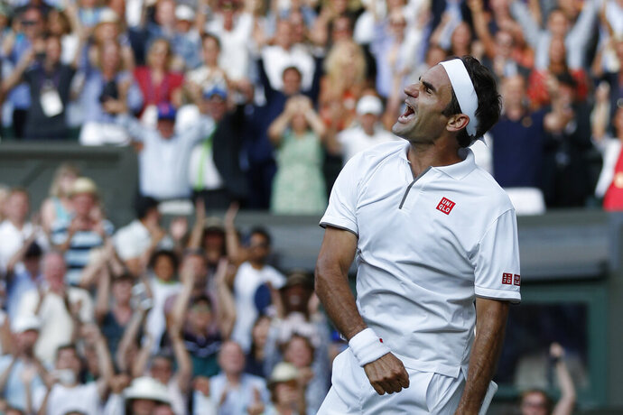 Switzerland's Roger Federer celebrates after beating Spain's Rafael Nadal in a Men's singles semifinal match on day eleven of the Wimbledon Tennis Championships in London, Friday, July 12, 2019. (Adrian Dennis/Pool Photo via AP)