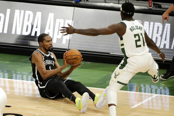 Brooklyn Nets' Kevin Durant, left, looks to pass against Milwaukee Bucks' Jrue Holiday, right, after falling to the floor during the second half of an NBA basketball game Tuesday, May 4, 2021, in Milwaukee. (AP Photo/Aaron Gash)