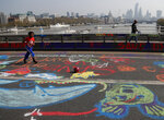 A boy plays football on graffiti drawn by protestors who blocked Waterloo Bridge in London, Wednesday, April 17, 2019, with the River Thames and the city on London in background. The group Extinction Rebellion is calling for a week of civil disobedience against what it says is the failure to tackle the causes of climate change. (AP Photo/Frank Augstein)