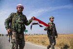 Syrian government forces carry a national flag as they man a checkpoint near the town of Tal Tamr, north Syria, Tuesday, Oct. 22, 2019. Russia and Turkey announced an agreement Tuesday to jointly patrol almost the entire northeastern Syrian border after the withdrawal of Kurdish fighters, cementing the two countries' power in Syria in the wake of President Donald Trump's abrupt withdrawal of U.S. forces. (AP Photo/Baderkhan Ahmad)