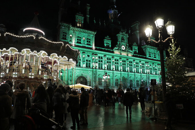FILE - In this Dec.12 2020 file photo, people wait by a carousel set up for Christmas while the Paris town hall gets green lightings to celebrate the fifth anniversary of the international pact aimed at curbing global warming. The French Prime Minister has suggested that parents concerned about the welfare of vulnerable relatives take their kids out of school from Thursday, to begin a eight-day period of protective confinement before Christmas family gatherings. (AP Photo/Lewis Joly, File)