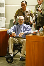 FILE - In this Jan.6, 2017 file photo real estate heir Robert Durst is wheeled into a courtroom in a Los Angeles Superior Court Airport Branch in Los Angeles. Durst faces trial in the slaying of his best friend 20 years ago. Jury selection begins Wednesday, Jan.19, 2020, in Los Angeles.  (Mark Boster/Los Angeles Times via AP, Pool,File)