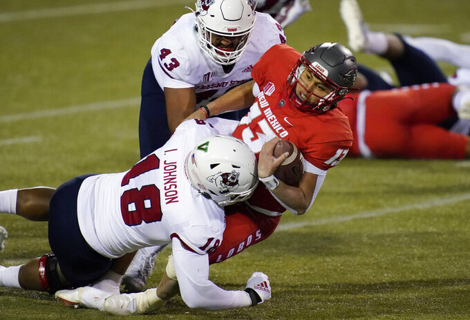 Fresno State defensive lineman Isaiah Johnson (18) and defensive lineman Alex Dumais (43) tackle New Mexico quarterback Isaiah Chavez (13) during the first half of an NCAA college football game Saturday, Dec. 12, 2020, in Las Vegas. (AP Photo/John Locher)