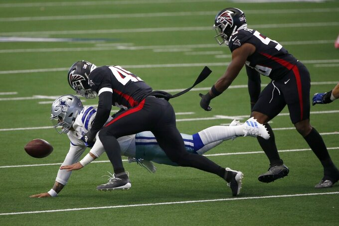 Dallas Cowboys quarterback Dak Prescott (4) fumbles the ball after being sacked by Atlanta Falcons linebacker Deion Jones (45) with help from defensive end Dante Fowler Jr. (56) in the first half of an NFL football game in Arlington, Texas, Sunday, Sept. 20, 2020. (AP Photo/Ron Jenkins)