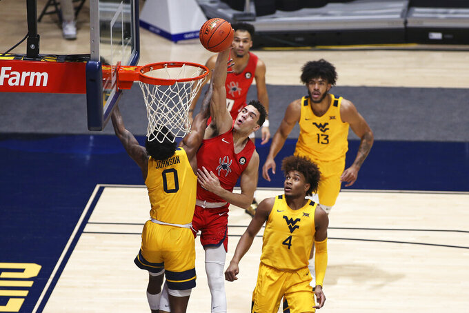 Richmond forward Tyler Burton (3) shoots while defended by West Virginia guards Kedrian Johnson (0) and Miles McBride (4) during the second half of an NCAA college basketball game Sunday, Dec. 13, 2020, in Morgantown, W.Va. (AP Photo/Kathleen Batten)