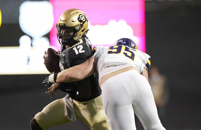 Colorado quarterback Brendon Lewis, left, is sacked by Northern Colorado defensive lineman Joe Golden in the first half of an NCAA college football game Friday, Sept. 3, 2021, in Boulder, Colo. (AP Photo/David Zalubowski)