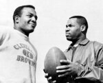 FILE - In this Jan. 11, 1964, file photo, fullback Jim Brown, left, and flanker back Bobby Mitchell, once a feared duo for the Cleveland Browns before Mitchell was dealt to Washington, are back together as teammates, as they prepare for the annual Pro Bowl at Los Angeles. Mitchell, the speedy late 1950s and '60s NFL offensive star the Browns and the Washington Redskins, has died. He was 84. The Pro Football Hall of Fame said Sunday night, April 5, 2020, that Mitchell's family said he died in the afternoon. (AP Photo/Harold Filan, File)